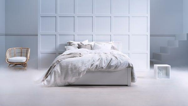 Bilik dengan katil bantal dan peralatan tempat tidur di sebelah lampu lantai