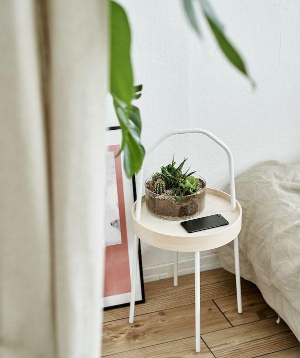 Meja sisi dengan terrarium di dalam bilik tidur berwarna putih