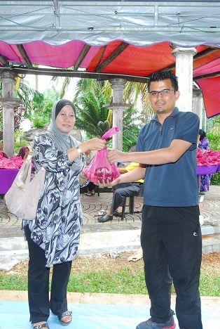 SUB BKP Puan Halizah Binti Sipun wakil Pejabat SUK Perak menyerahkan bungkusan daging korban kepada Jawatankuasa Pengagihan Daging Korban En Khir Johari